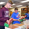Faith Christian Academy junior Sawyer Smith packs boxes alongside Andrew Rosenbaum, of Thrivent Financial, a sponsor of the event.  Debby High — For Digital First Media