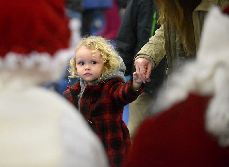 Two-year-old Leah Glass holds her mother's hand as she tries to decide whether or not she wants to visit with Santa and Mrs. Claus at the Sellersville Firehouse during Winterfest Dec. 6, 2016.   |   Bob Raines--Digital First Media