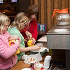 Jocelyn Manthel, 9, left, joins her twin sister, Chloe Manthel, in putting mustard on their hot dog lunches. They are helped by their grandmother, Lillian Higgins, a member of the Ladies Auxiliary Post 3612 who brought all four of her grandchildren to the Christmas Party event.  Rachel Wisniewski — For Digital First Media