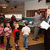 Children between the ages of 4 and 7 line up for their chance to meet and receive a gift from Santa Claus. Commander Ed Heary, right, organizes the line.  Rachel Wisniewski — For Digital First Media
