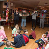 Children sit and listen to instructions from event organizer Commander Ed Heary, standing left. Heary explains that before Santa Clause arrives to the party, the group will recite the pledge of allegiance.  Rachel Wisniewski — For Digital First Media