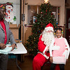 Precious Oluwole, 7, grins while sitting on Santa's lap. Beside her, Quartermaster Emmett Mayo prepares to hand her a gift.  Rachel Wisniewski — For Digital First Media