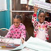 Sisters Galisa, 5, left, and Janay, 6, excitedly hold up the gifts that they just received from Santa Clause: a desktop drum set and an electronic keyboard.  Rachel Wisniewski — For Digital First Media