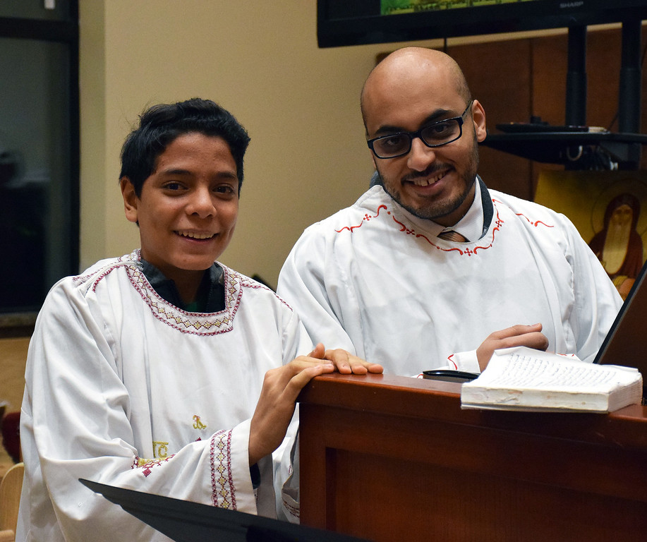 . Deacon\'s - David ElBardissi and Pepeto Ibrahim read prayers during the prayer vigil on Monday night. Debby High for Digital First Media