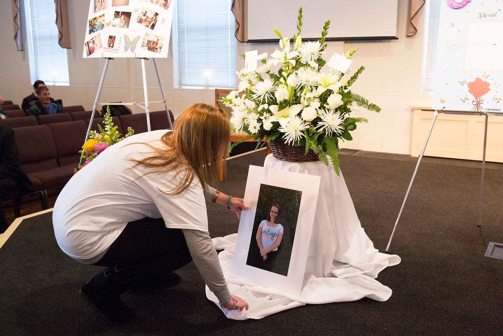 . Inside the New Life Presbyterian Church, a woman adds a large printed photograph of Grace Packer to an elaborate memorial display of photographs, flowers, paintings, and collages made and donated by friends, family, and community members. Rachel Wisniewski � For Digital First Media