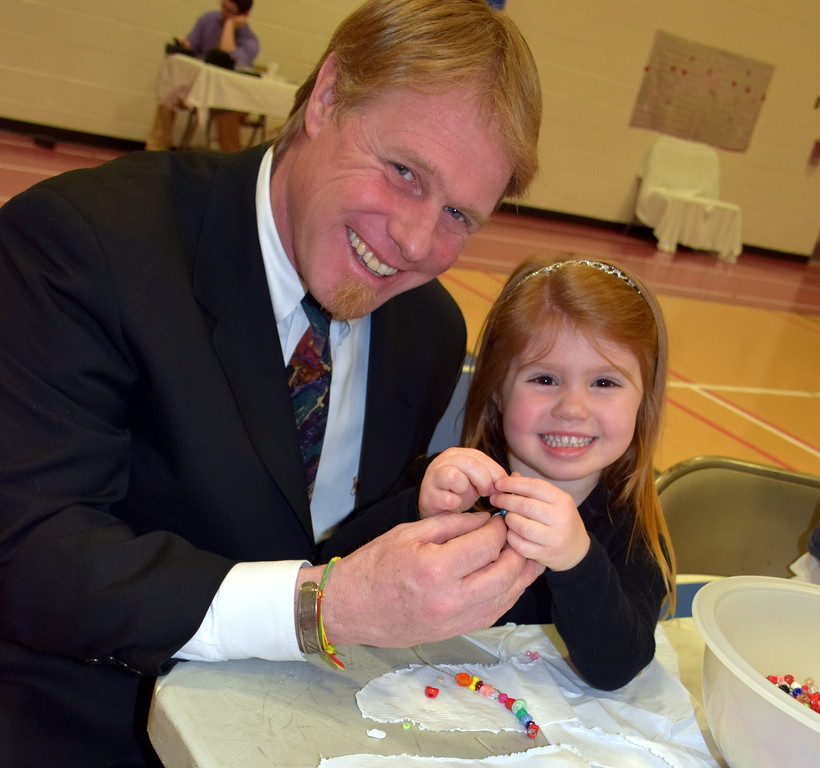 . Jeff and Sierra Walker make necklaces before stepping on the dance floor during the Daddy Daughter Dance at the Indian Valley Family YMCA Saturday, Feb. 11.  Debby High � For Digital First Media