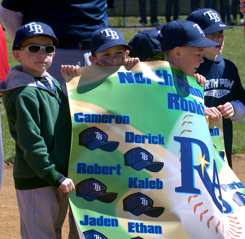 . (Bob Raines--Digital First Media)___ North Penn Little League Rookies t-ballers parade their team banner on opening day at Senator Field April 8, 2017.