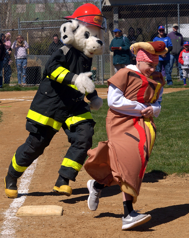 . (Bob Raines--Digital First Media)___ The Hatfield Hot Dog takes the lead as he and Sparky  race the bases during the North Penn Little League Opening Day festivities.