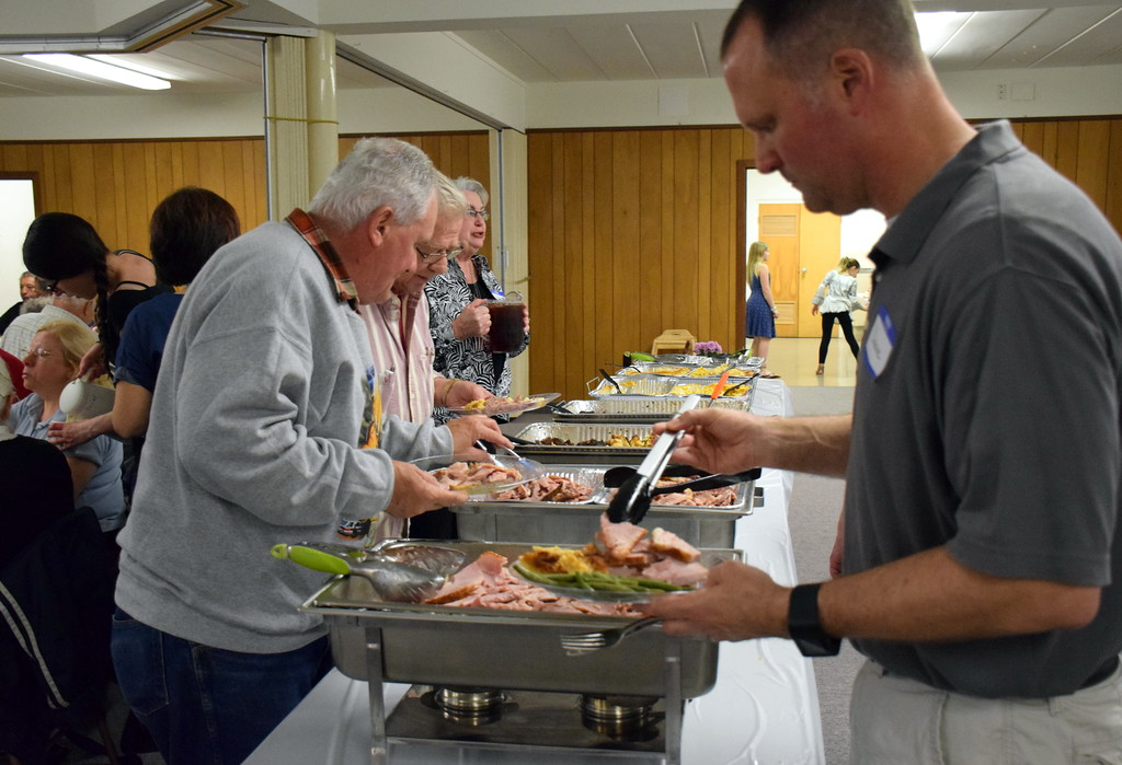 . Grace Bible Church volunteers gather plates to serve during the annual free community Easter dinner at Grace Bible Church in Souderton Saturday, April 15.  Debby High � For Digital First Media