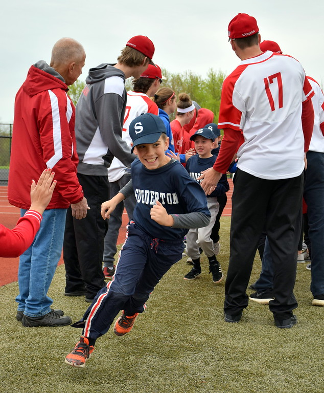 . Players charge out onto the field during Souderton Area Baseball League�s opening day ceremony at Souderton Area High School Saturday, April 22. Debby High � For Digital First Media