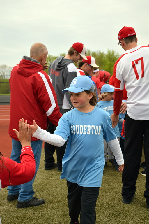. Souderton Area High School players greet Souderton Area Baseball League players as they march onto the field during the opening day ceremony Saturday, April 22. Debby High � For Digital First Media