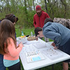 Attendees gather around the Students for a Sustainable Future table to look at the recently caught macroinvertebrates (animals that live underwater with no backbone) at the Jarrett Nature Center's 15th anniversary and Earth Day celebration April 22.  Christine Wolkin — For Digital First Media