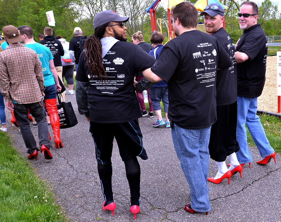 . Four walkers link arms for mutual support as they take part in the Walk A Mile In Her Shoes event benefitting Laurel House in Heebner Park, Worcester May 6, 2017.  (Bob Raines/Digital First Media)