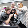 Paige Wills, 15, plays a trivia game on her phone while Sarah Sienko and Jamie Cooney from Platinum Salon put temporary purple highlights in her hair. This is the first year that Platinum Salon paired with Salon l'Etoile to offer participants haircuts, hair coloring, manicures and makeup, all at no charge.  Rachel Wisniewski — For Digital First Media