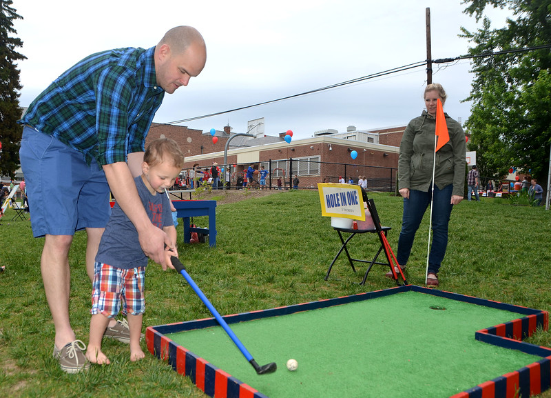 Joe Swaim, of Jenkintown, shows his 2-year-old son, Vinny, how to putt during the Jenkintown Red and Blue Fair at Jenkintown Elementary School May 20.  Christine Wolkin — For Digital First Media