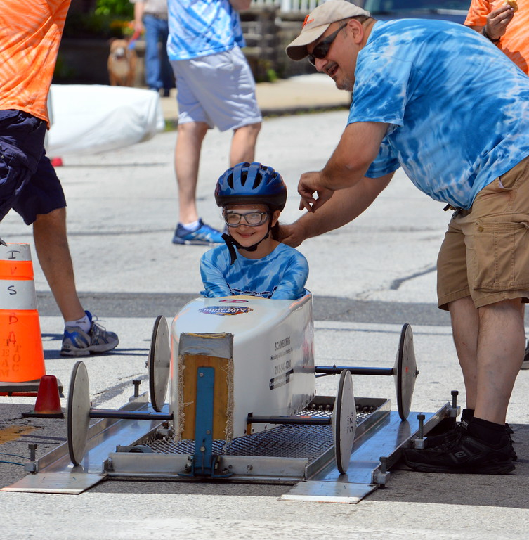 . Indian Valley Soap Box Association board Director Marc DeRosa helps his daughter, Maria, get ready to race in the Indian Valley Soap Box Derby in Souderton Saturday, June 3.  Debby High � For Digital First Media