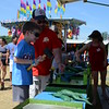 Connor Cozzo gets ready to catapult a frog into the pond with the help of his father, Steve Cozzo, both of Huntingdon Valley, at the June Fete Fair June 11.  Christine Wolkin — For Digital First Media