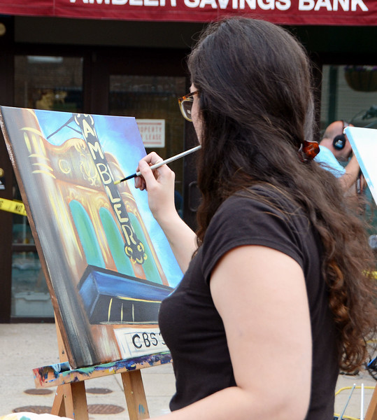 Nicole Asay, of Perkasie, paints an oil on canvas of the iconic Ambler Theater during Ambler's Arts & Music Festival June 16.  Christine Wolkin — For Digital First Media