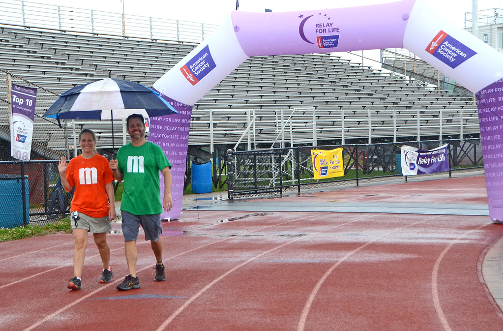 . Crystal and Tom McKee, of Lansdale, pass beneath the archway during the North Penn Relay for Life at the high school\'s Crawford Stadium Saturday, June 17.  Christine Wolkin - For Digital First Media