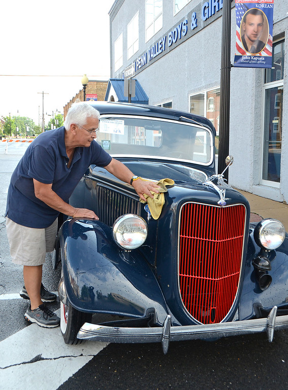 . Ron Torres of East Coventry wipes the rain from his 1936 Ford Pickup during Lansdale\'s Under the Lights Car Show Saturday, June 16.  Christine Wolkin - For Digital First Media