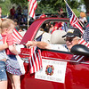 Bill Marren, a member of the Veterans of Foreign Wars Post 676, right, is greeted by family members as his float momentarily comes to a stop.  Rachel Wisniewski — For Digital First Media