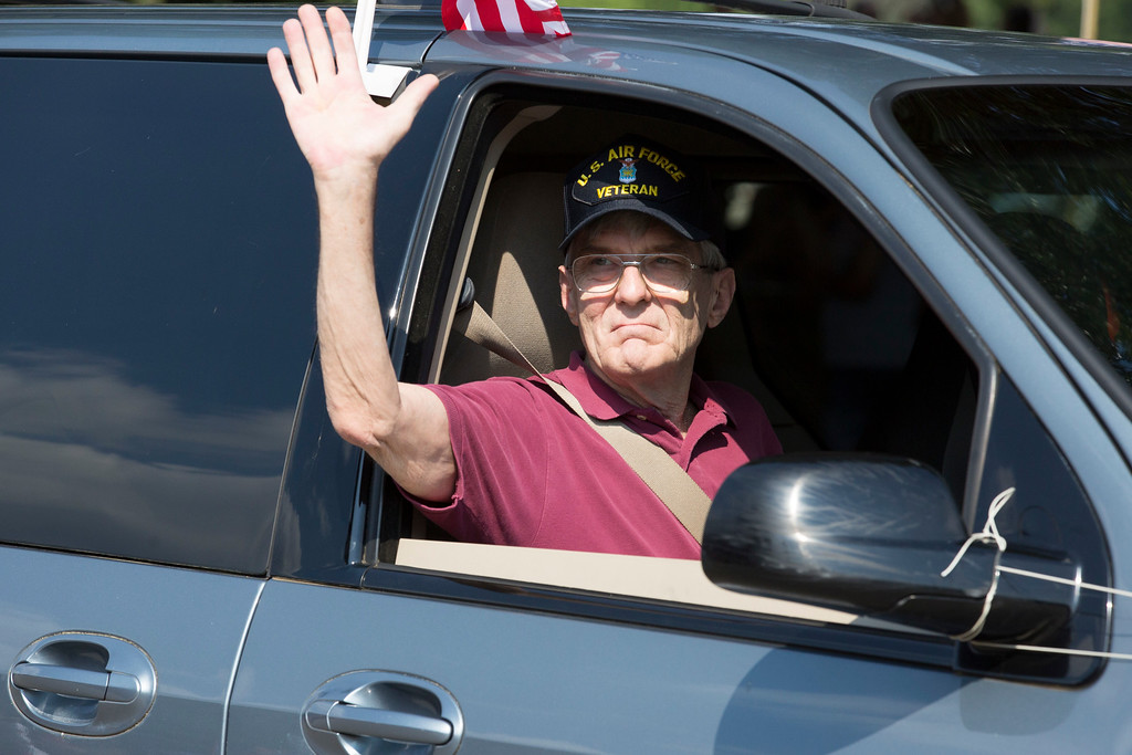 . A member of the Veterans of Foreign Wars Post 676 waves to the crowd.  Rachel Wisniewski � For Digital First Media
