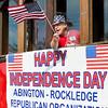 A man waves a flag from the Abington/Rockledge Republican Organization trolley.  Rachel Wisniewski — For Digital First Media
