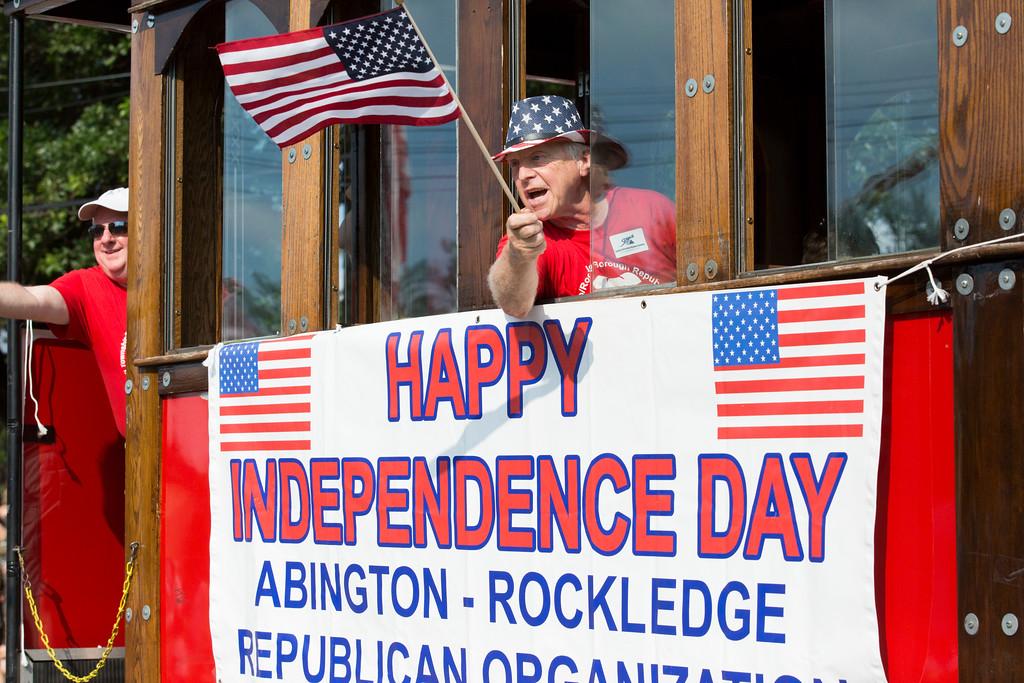 . A man waves a flag from the Abington/Rockledge Republican Organization trolley.  Rachel Wisniewski � For Digital First Media