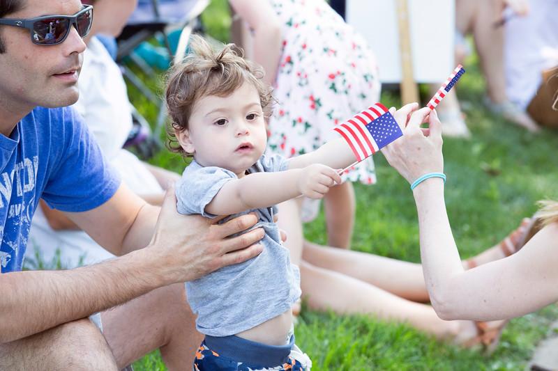 Reid Herzog, 18 months, shows his patriotism by waving two miniature American flags.  Rachel Wisniewski — For Digital First Media