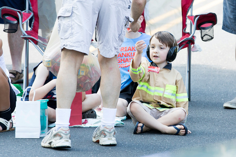 Ash Sommers, 4, dressed in a firefighter's costume, receives a piece of candy from a member of the parade.  Rachel Wisniewski — For Digital First Media