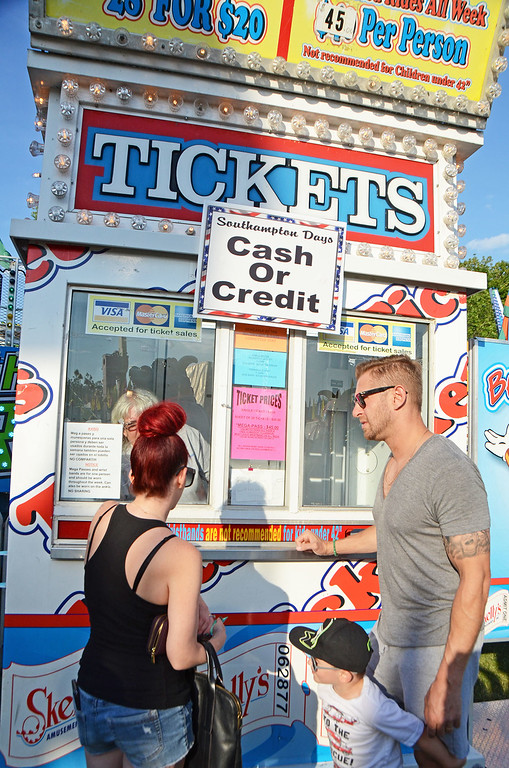 . The Lowinger family purchases ride tickets at the Southampton Days Fair July 3.  Christine Wolkin � For Digital First Media