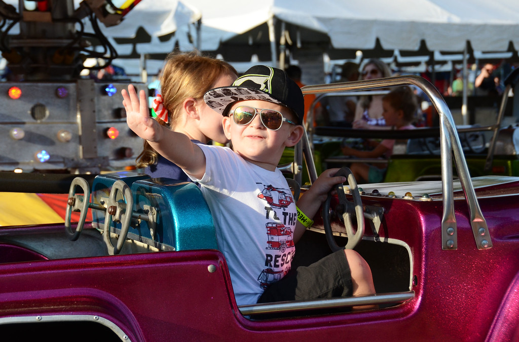. Jaxon Lowinger, of Hatboro, waves to his parents as he rides the cars during the Southampton Days Fair July 3.  Christine Wolkin � For Digital First Media