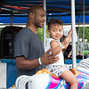 Daley Staples, 2, rides the merry-go-round with her father, Akeiff.  Rachel Wisniewski — For Digital First Media
