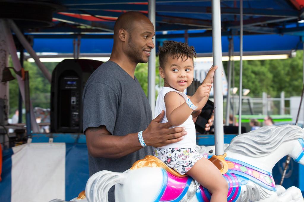. Daley Staples, 2, rides the merry-go-round with her father, Akeiff.  Rachel Wisniewski � For Digital First Media