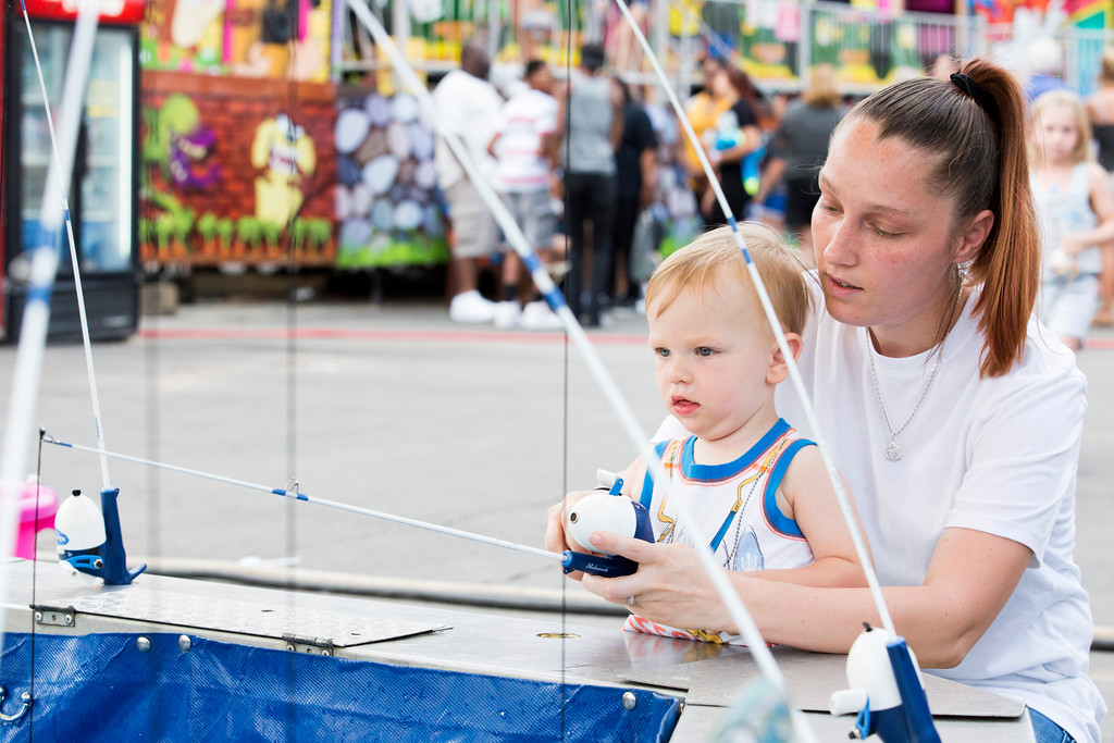 . Lukas West gets help with a fishing game from his mother, Christina.  Rachel Wisniewski � For Digital First Media