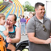 Christy and Camryn Warren, 3, cheer on Chris Warren, right, as he competes in a balloon dart game.  Rachel Wisniewski — For Digital First Media