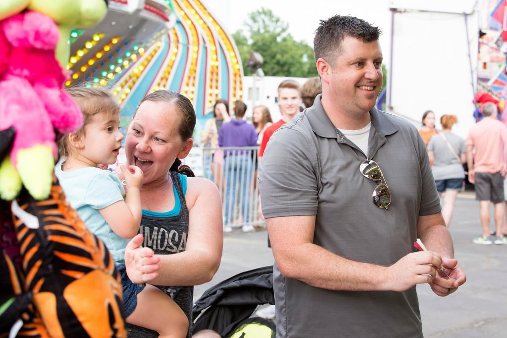 . Christy and Camryn Warren, 3, cheer on Chris Warren, right, as he competes in a balloon dart game.  Rachel Wisniewski � For Digital First Media