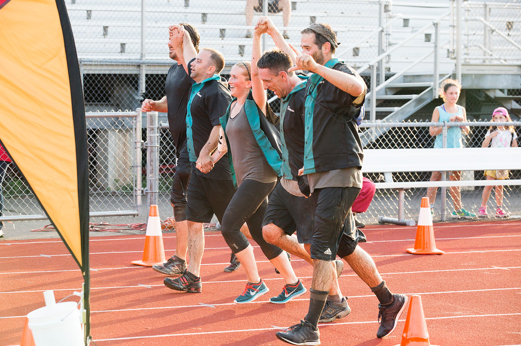 . Members of the King Pins team, aptly dressed in bowling shirts, hold hands as they cross the finish line of the Tribal Challenge.  Rachel Wisniewski � For Digital First Media
