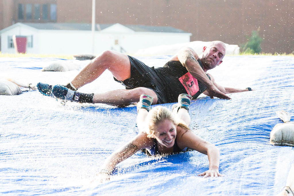 . Members of the team Black and Blue complete the 21st challenge: a massive slip and slide.  Rachel Wisniewski � For Digital First Media