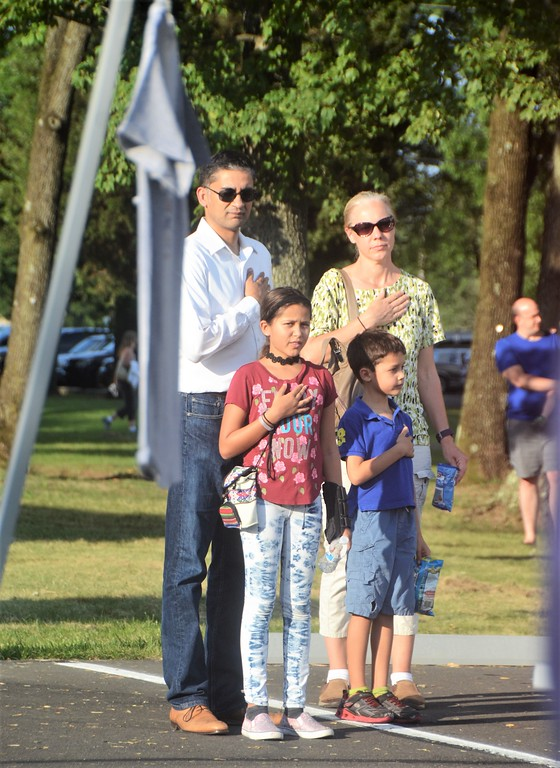 . The Rao family, of Maple Glen, pay their respects during the flag ceremony at Horsham�s National Night Out Aug. 1 outside the Horsham Municipal Complex.  Christine Wolkin � For Digital First Media