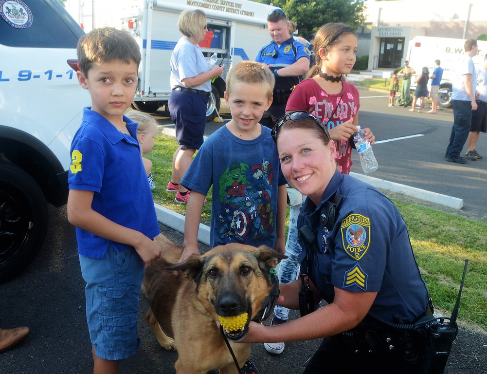 . Everett Rao, of Maple Glen, left, and Dylan Augustine, of Hatboro, are introduced to Bella, one of Abington police�s K-9 dogs by Sgt. Jennifer Doyle during Horsham�s National Night Out Aug. 1 outside the Horsham Municipal Complex.  Christine Wolkin � For Digital First Media