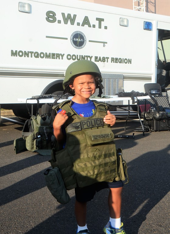 . Major White, of Horsham, tries on a S.W.A.T. vest outside the Montgomery County East Region S.W.A.T. Team van during Horsham�s National Night Out Aug. 1 outside the Horsham Municipal Complex.  Christine Wolkin � For Digital First Media