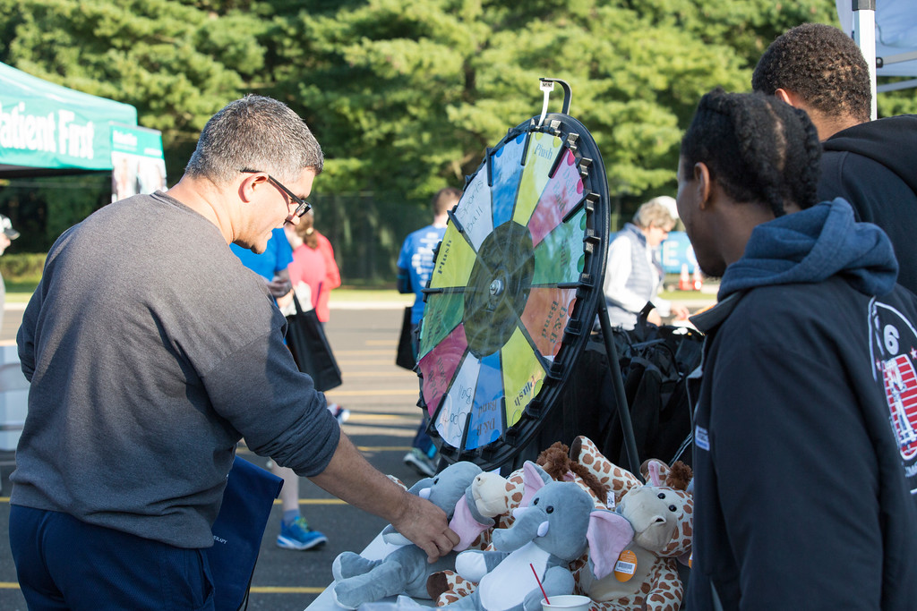 . Michael Prasad, left, wins a free stuffed animal from a Dave & Busters table at the Run with the Sun race at Manor College.  Rachel Wisniewski � For Digital First Media