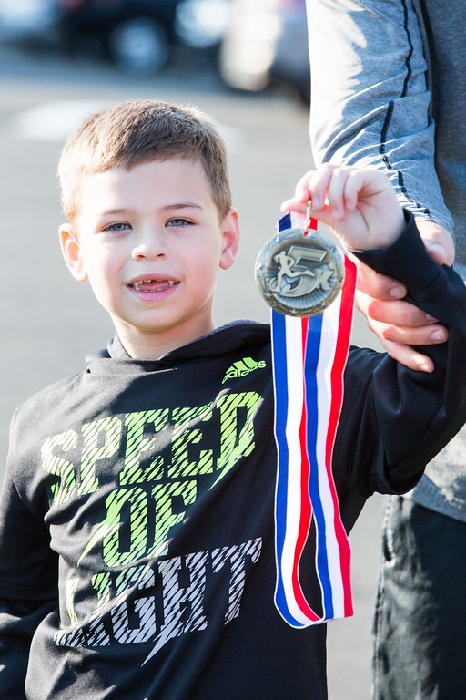 . Eddie Bongard, 7, proudly holds the medal he won for finishing first in his age group (14 years and younger), with a time of 31:53, at the Run with the Sun 5K.  Rachel Wisniewski � For Digital First Media