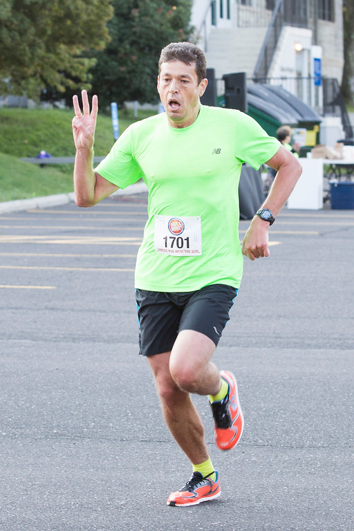 . Vitaly Belotserkovs, 46, makes a gesture as he prepares to cross the finish line of the Run in the Sun 5K race on the morning of Sept. 10. Velotserkovs finished the race in first place with a time of 19:06.  Rachel Wisniewski � For Digital First Media