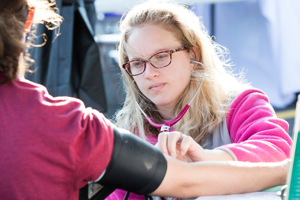 . Alex Kane, a medical assistant with Patient First, administers a free blood pressure check on runner Erin Regan, left, during the Run with the Sun 5K. Patient First provided free blood pressure checks at the race to promote health awareness.  Rachel Wisniewski � For Digital First Media