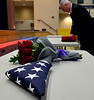 A folded United States flag and bouquet of roses lies on a table as Pennsylvania State Representative Tom Murt, R-152nd, prepares for the ceremony dedicating a section of Byberry Rd. in Upper Moreland to the memory of Maj. Jeffrey Toczylowski April 1, 2017.  (Bob Raines / Digital First Media)