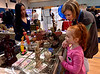Volunteer Alyssa Choing stands by to answer questions at the Cambodia table while Paityn Sullivan and her mother, Alexa, look at items at the International Spring Festival April 22, 2017.  (Bob Raines/Digital First Media)