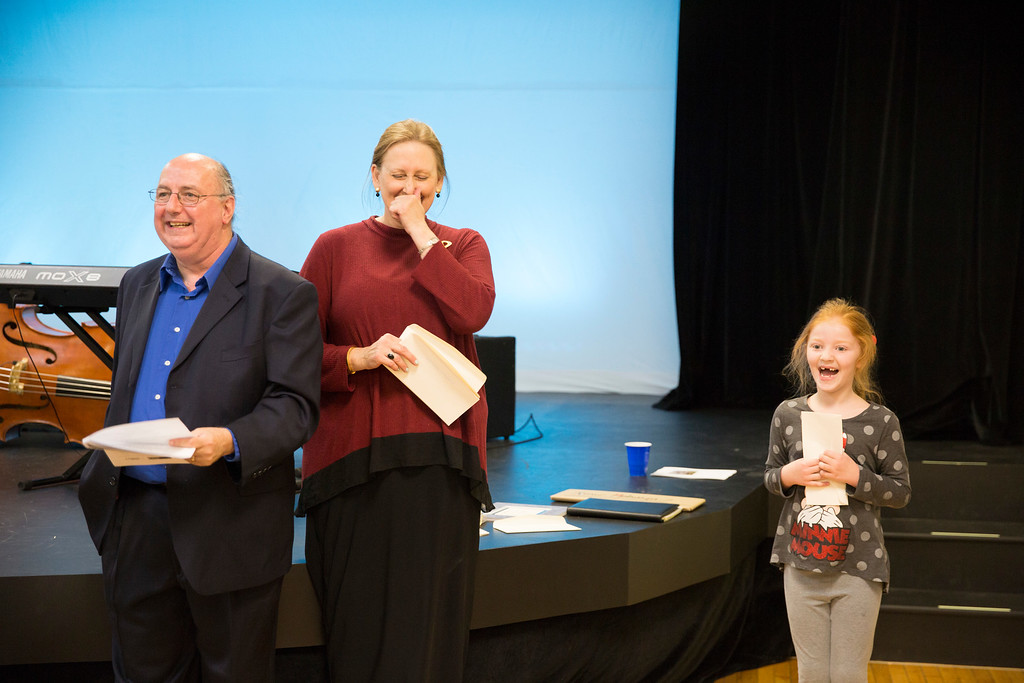 . Caroline Reid (right), the winner of the G1: grades K-4 portion of the Junior Artists Awards is giddy as she receives her award from Ed Kane and Rhonda Garland. (Rachel Wisniewski/For Digital First Media)