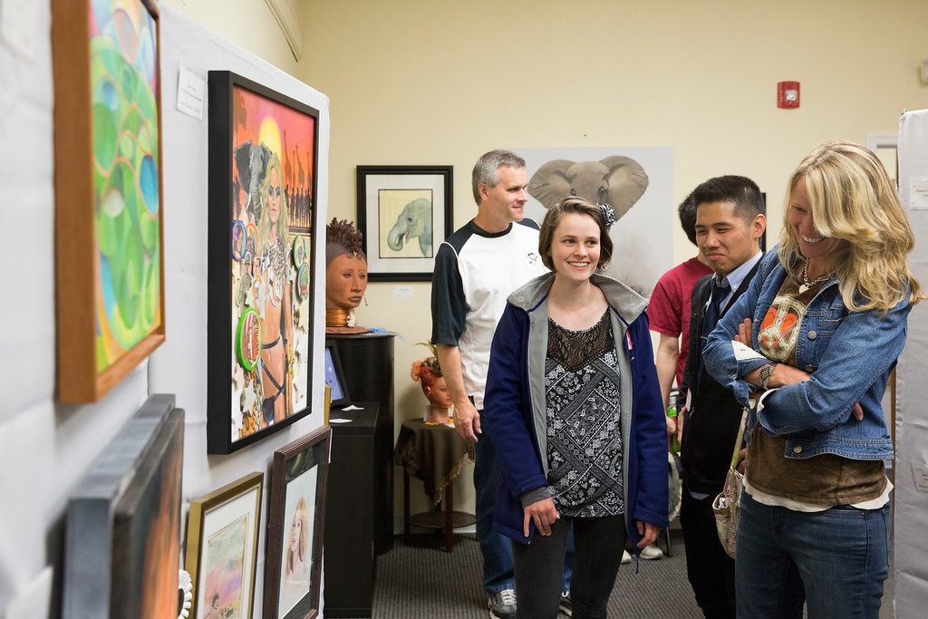 . Ashley Walter (center) joins her parents, Jim and Robin, and friends, John and Jeremy, in viewing artwork at the Spring Members� Exhibition. Ashley had an acrylic ink piece in the show titled �Head of Stoney Goblin-Dragon.� (Rachel Wisniewski/For Digital First Media)